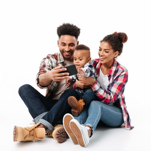 Full length portrait of a happy young african family with their little son taking a selfie while sitting together isolated over white background