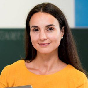 smiley-teacher-standing-classroom
